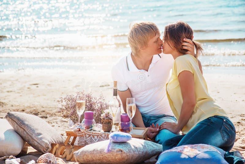 Le giovani coppie felici che godono del picnic sulla spiaggia ed hanno buon Ti immagini stock libere da diritti