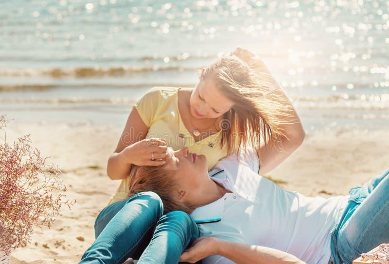 Le giovani coppie felici che godono del picnic sulla spiaggia ed hanno buon Ti fotografia stock