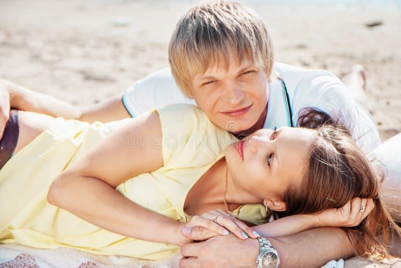Le giovani coppie felici che godono del picnic sulla spiaggia ed hanno buon Ti immagine stock