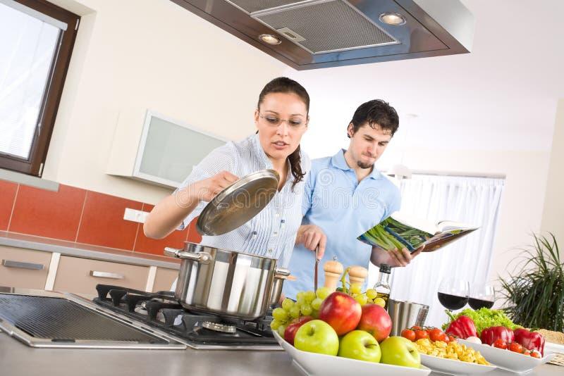 Le giovani coppie felici cucinano in cucina con il libro di cucina immagini stock libere da diritti