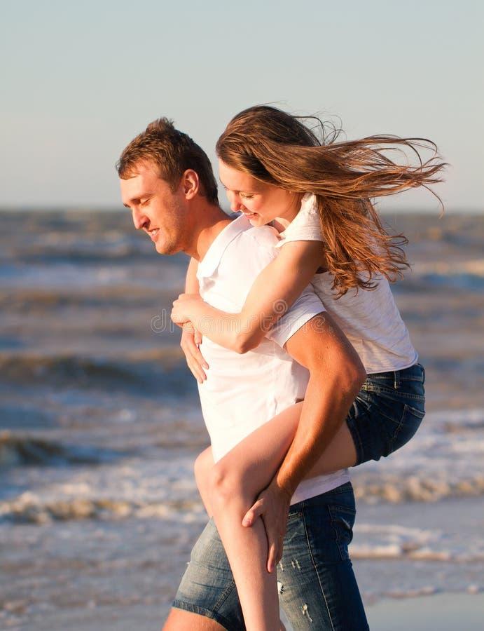 Le giovani coppie felici nell'amore si divertono sulla bella spiaggia al beauti fotografia stock libera da diritti