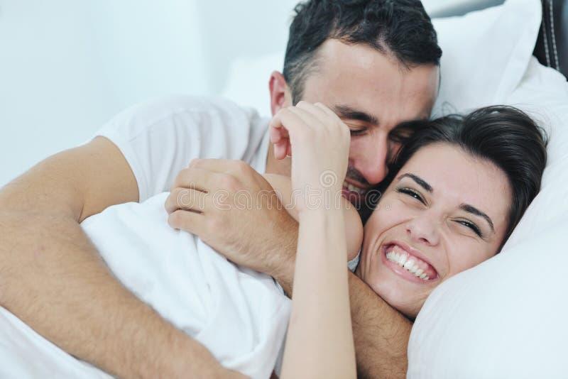 Le giovani coppie hanno buon tempo nella loro camera da letto immagini stock libere da diritti