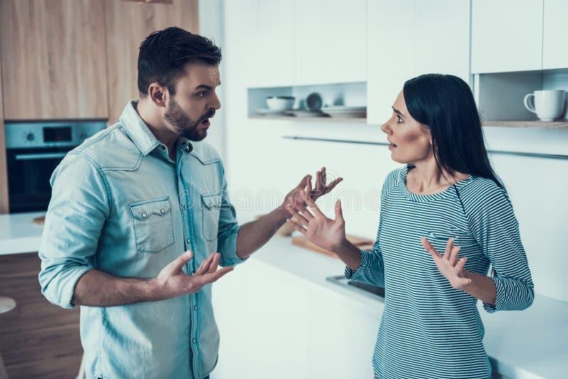 Le giovani coppie hanno disaccordo in cucina a casa fotografia stock libera da diritti
