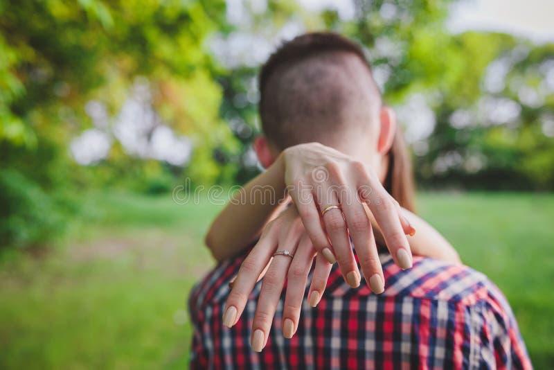 Le giovani coppie nell'amore che cammina in autunno parcheggiano tenersi per mano fotografie stock