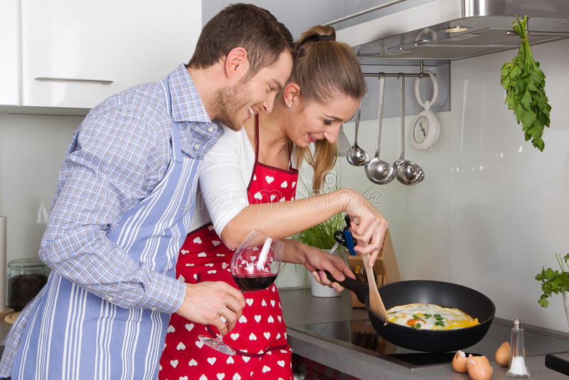 Le giovani coppie nell'amore che cucina insieme nella cucina ed hanno fu fotografia stock