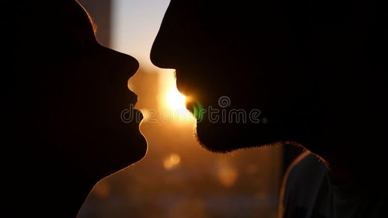 Le giovani coppie nell'amore, si esaminano occhi del ` s, contro il tramonto, con l'effetto di una lente Esegue un dito giù immagini stock libere da diritti