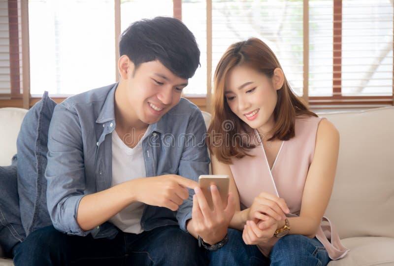 Le giovani coppie o amico asiatiche che sembrano il telefono cellulare astuto con godono di al salone immagini stock