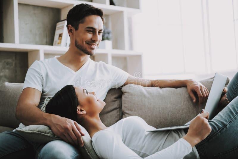 Le giovani coppie passano il tempo libero con il computer portatile a casa fotografia stock libera da diritti