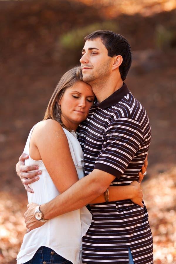 Le giovani coppie ripartono un abbraccio amoroso immagini stock libere da diritti