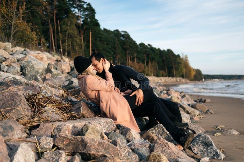 Le giovani coppie sessuali nell'amore che si riposa sulle pietre alla spiaggia, abbracciando baciare e si godono di fotografia stock