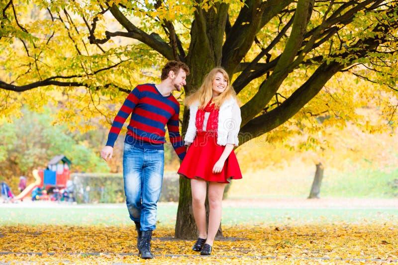 Le giovani coppie si incontrano in parco sul tenersi per mano della data immagine stock libera da diritti