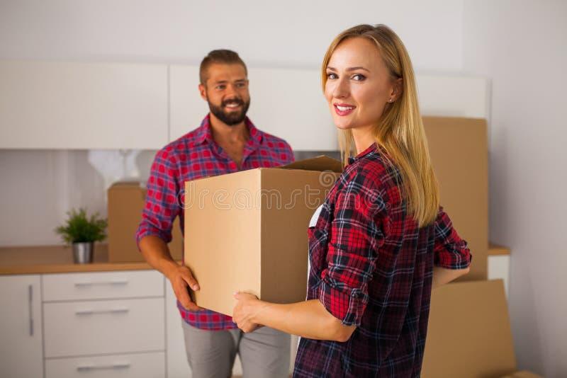 Le giovani coppie si muovono appena verso il loro nuovo appartamento Sono unpackin immagini stock