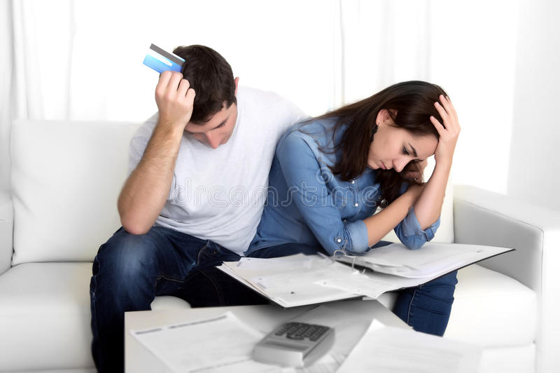 Le giovani coppie si sono preoccupate a casa nei pagamenti della banca di contabilità di sforzo fotografia stock libera da diritti