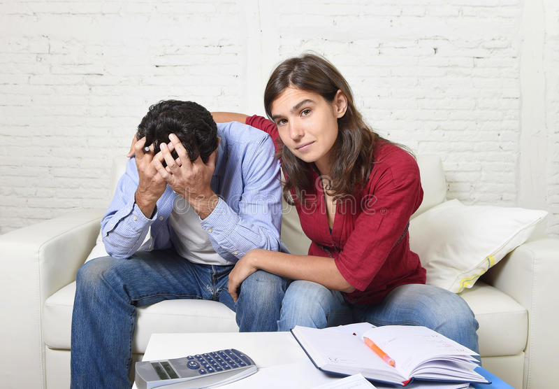 Le giovani coppie si sono preoccupate a casa nella moglie di sforzo che conforta le spese non pagate delle carte di banca delle f fotografia stock
