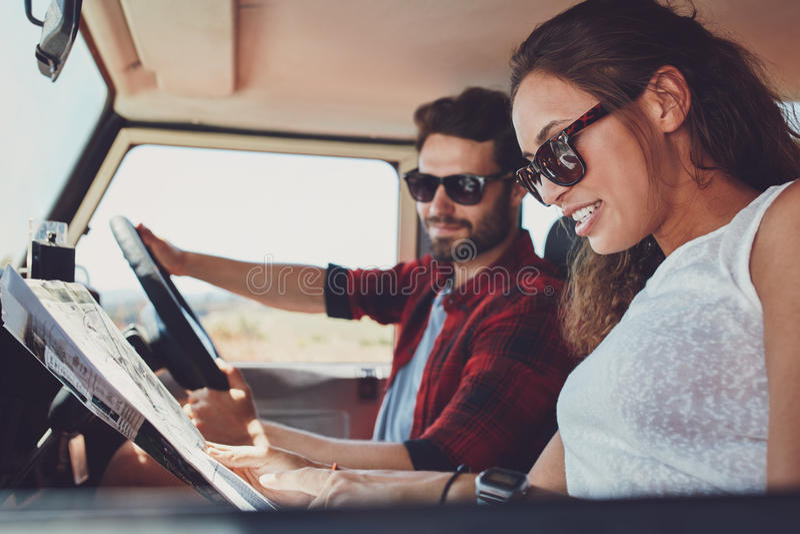 Le giovani coppie sulla lettura del roadtrip tracciano per le direzioni immagini stock libere da diritti