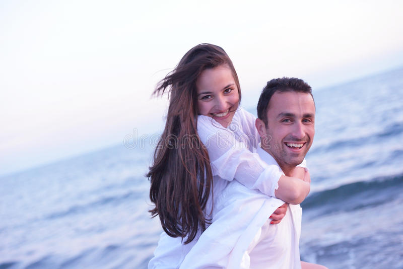 Le giovani coppie sulla spiaggia si divertono fotografia stock