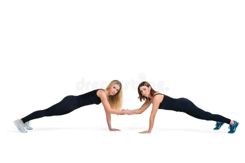 Le giovani donne allegre fanno la forma fisica spingere aumenta insieme immagine stock libera da diritti