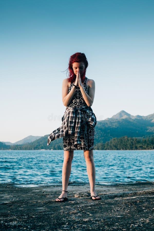 Le giovani donne con capelli rossi sta stando nella parte anteriore dell'oceano blu fotografia stock