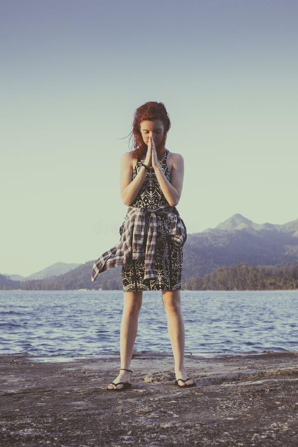 Le giovani donne con capelli rossi sta stando nella parte anteriore dell'oceano blu fotografia stock libera da diritti