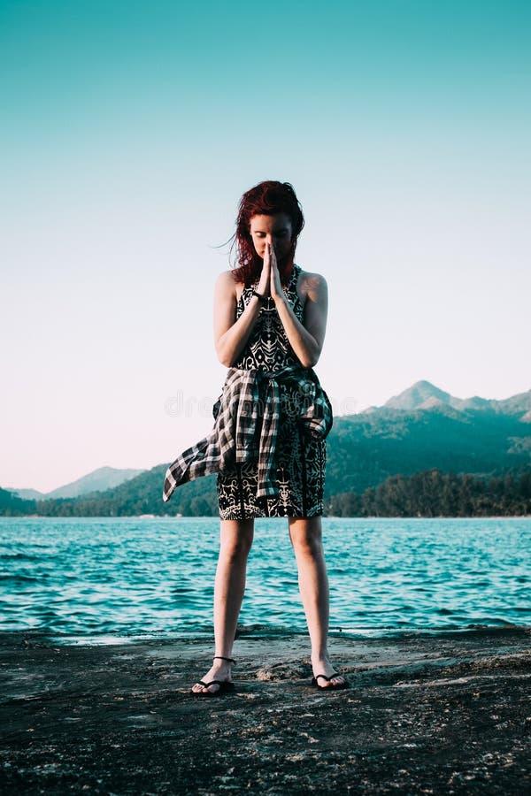 Le giovani donne con capelli rossi sta stando nella parte anteriore dell'oceano blu immagine stock