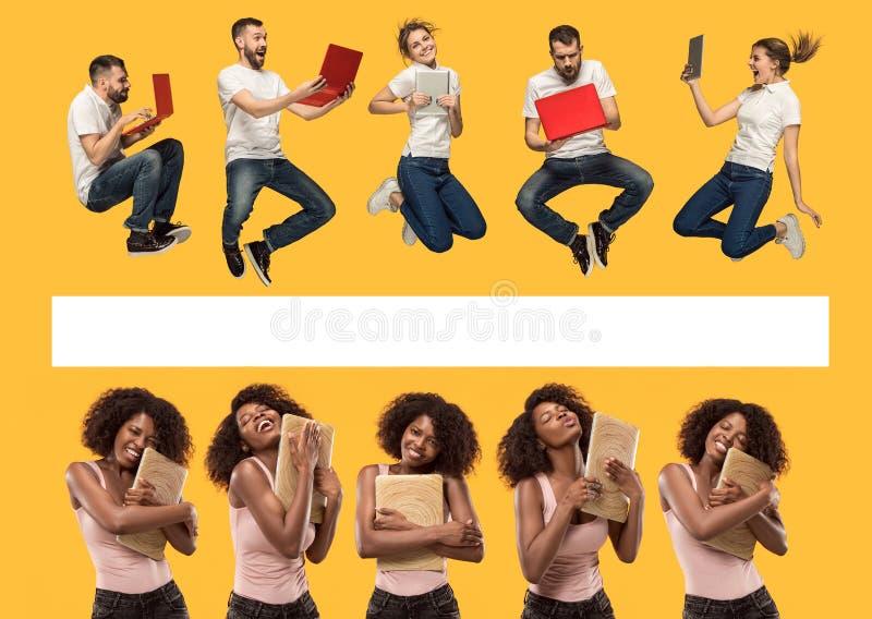 Le giovani donne ed uomini di salto felici con i computer portatili immagini stock