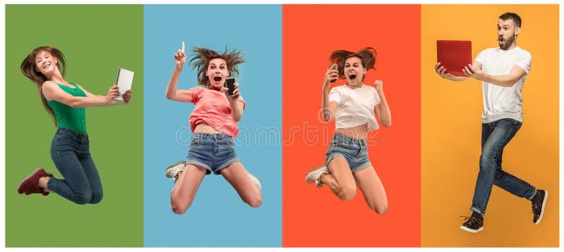 Le giovani donne ed uomo di salto felici con i computer portatili ed il telefono immagini stock libere da diritti