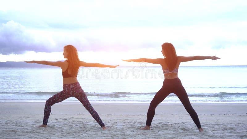Le giovani donne facendo l'yoga su un uso della spiaggia sport durano immagine stock