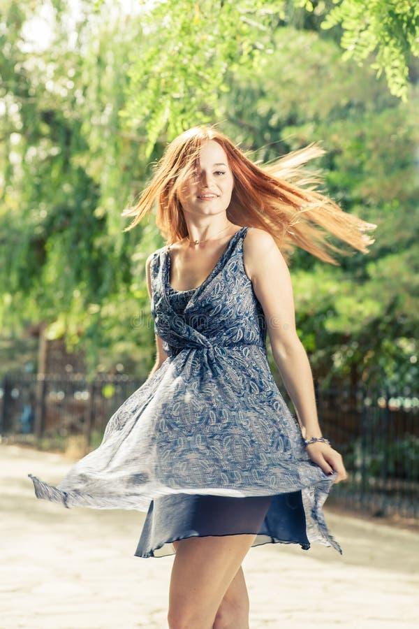 Le giovani donne graziose che ballano nel parco della città weared il vestito blu fotografia stock libera da diritti