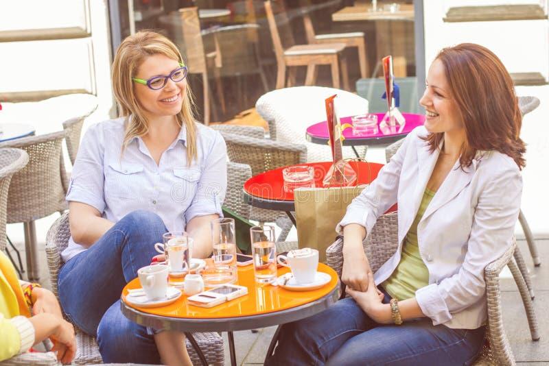 Le giovani donne hanno insieme pausa caffè fotografia stock