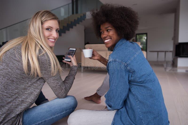 Le giovani donne multietniche si siedono sul pavimento e sul caffè bevente immagine stock libera da diritti