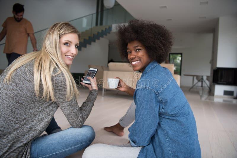 Le giovani donne multietniche si siedono sul pavimento e sul caffè bevente fotografia stock