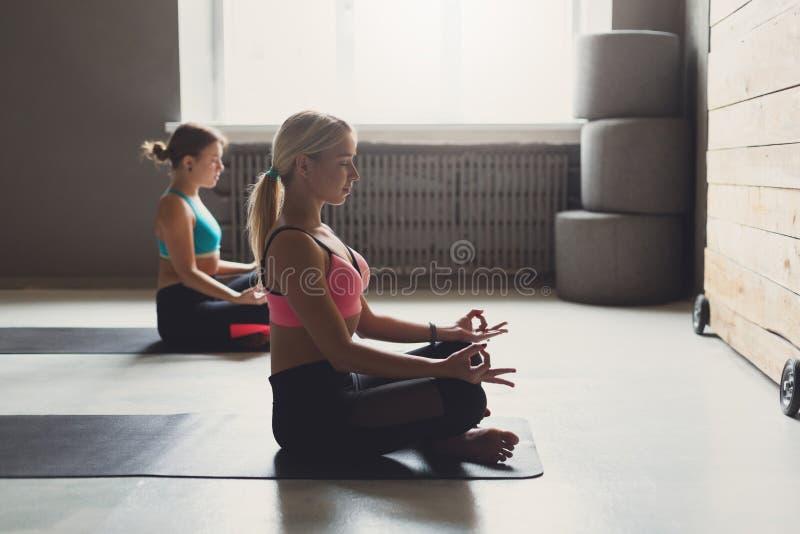 Le giovani donne nell'yoga classificano, si rilassano la posa di meditazione fotografie stock libere da diritti