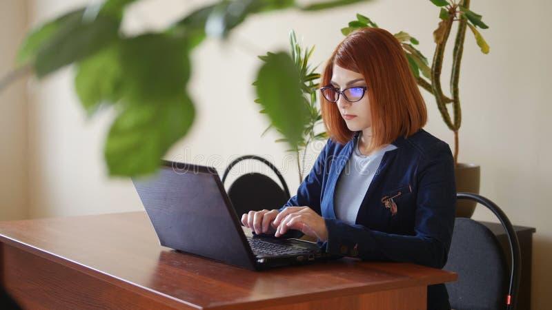 Le giovani donne rosse del officeworker dei capelli in vetri sta stampando sulla tastiera del computer portatile Metà di colpo co immagine stock