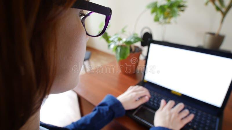 Le giovani donne rosse del officeworker dei capelli in vetri sta stampando sulla tastiera del computer portatile Sopra il colpo d fotografia stock libera da diritti