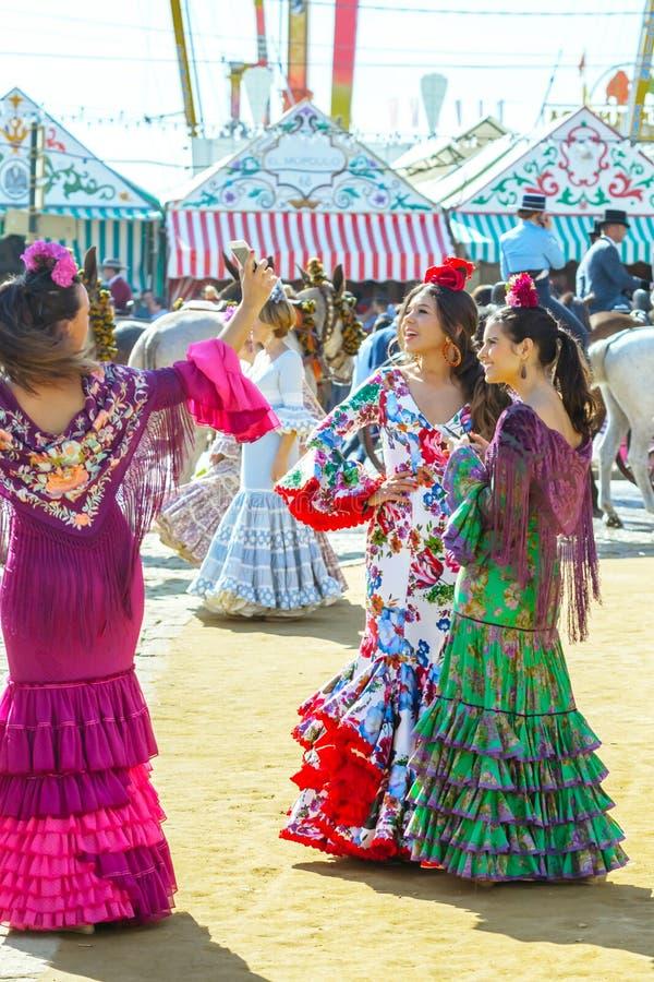 Le giovani donne si sono vestite in vestiti colourful alla Siviglia April Fair in Spagna fotografia stock