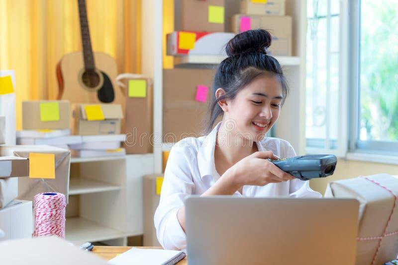 Le giovani donne sorridenti asiatiche gettano il prodotto della scatola dopo ordine dal cliente online vanno mirato a e successo, immagini stock