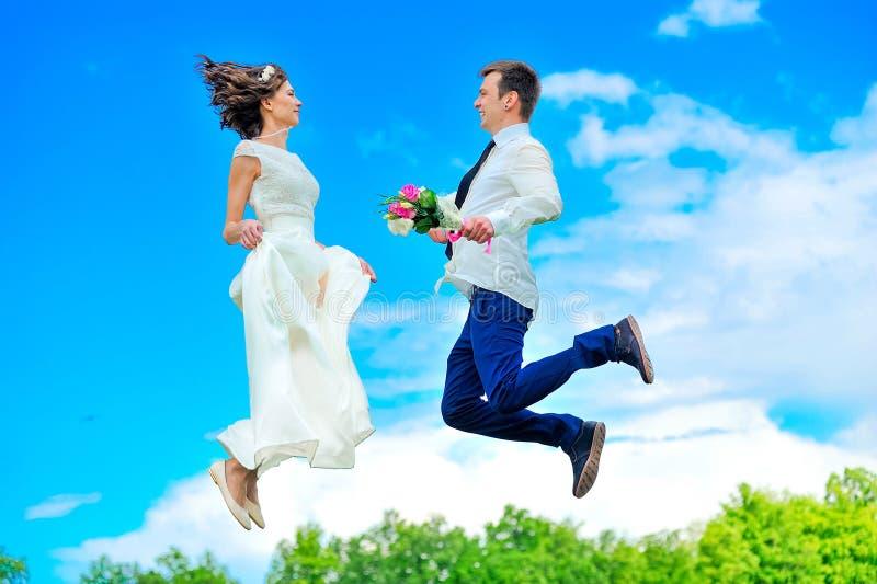 Le giovani e persone appena sposate belle stanno fluttuando nell'aria fotografie stock libere da diritti