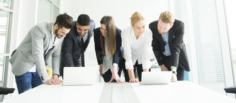 Le giovani persone di affari stanno nell'ufficio ed analizzano l'affare con riferimento a fotografie stock libere da diritti