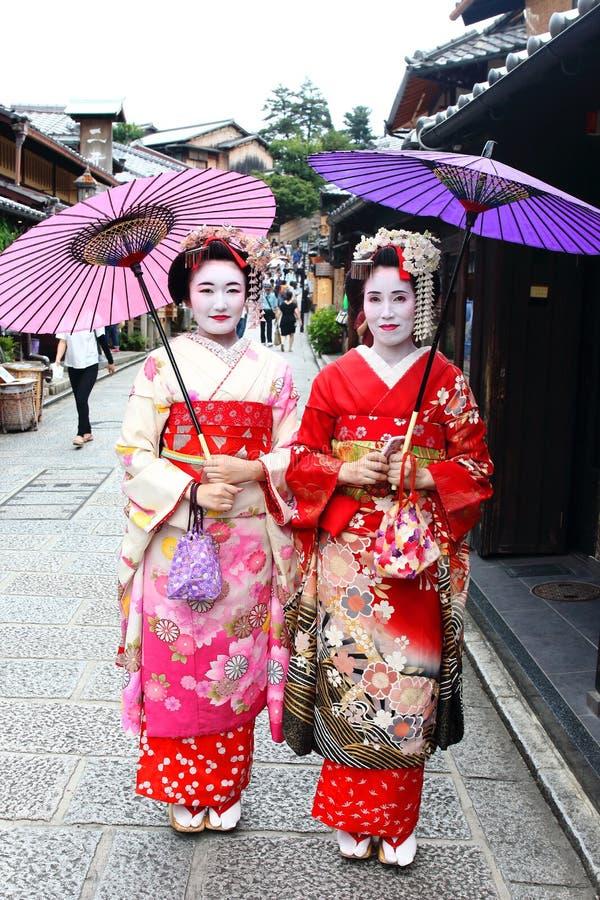 Le giovani ragazze giapponesi si sono vestite nell'abitudine del ` s della geisha che fa una passeggiata nelle strade pietra-pavi immagine stock libera da diritti