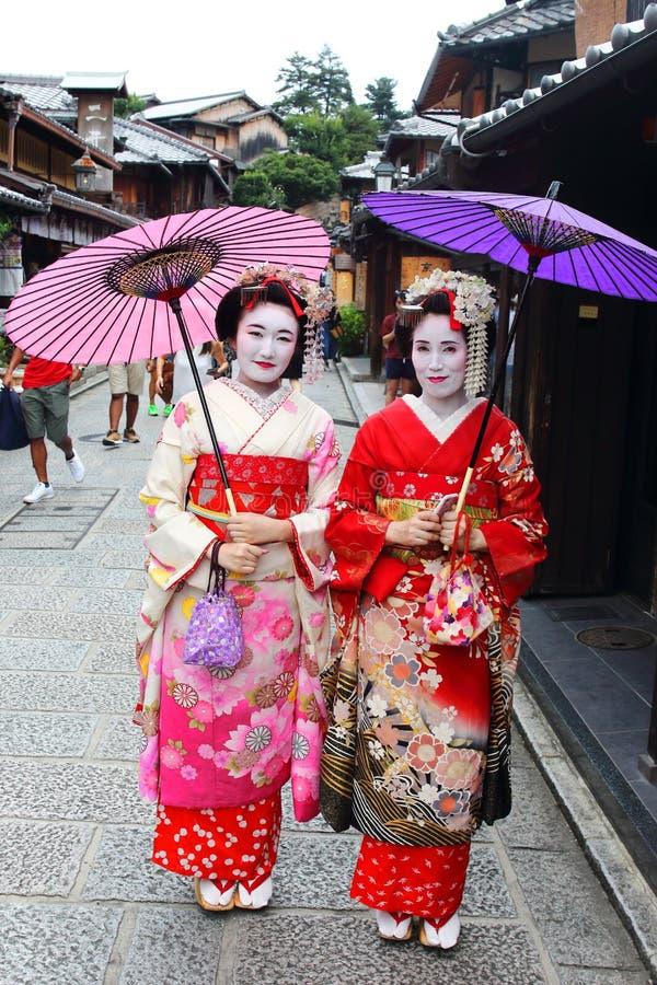 Le giovani ragazze giapponesi si sono vestite nell'abitudine del ` s della geisha che fa una passeggiata nelle strade pietra-pavi fotografia stock libera da diritti