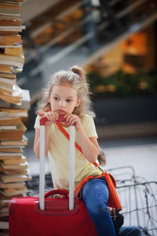 Le girlie avec du charme 7-8 ans se repose près de leur bagage à la station photos stock