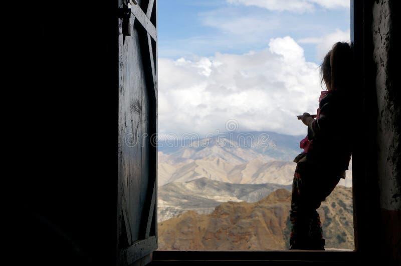 Le girlie népalais se tient dans la perspective de la porte et regarde les montagnes de l'Himalaya images stock