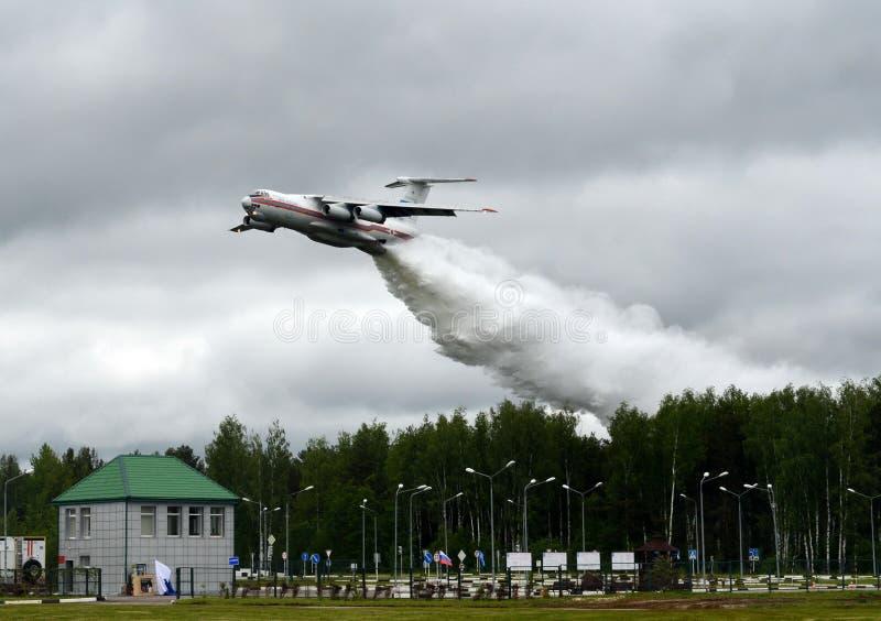 Le gocce degli aerei IL-76TD della lotta contro l'incendio innaffiano sopra la gamma del centro EMERCOM di salvataggio di Noginsk immagine stock