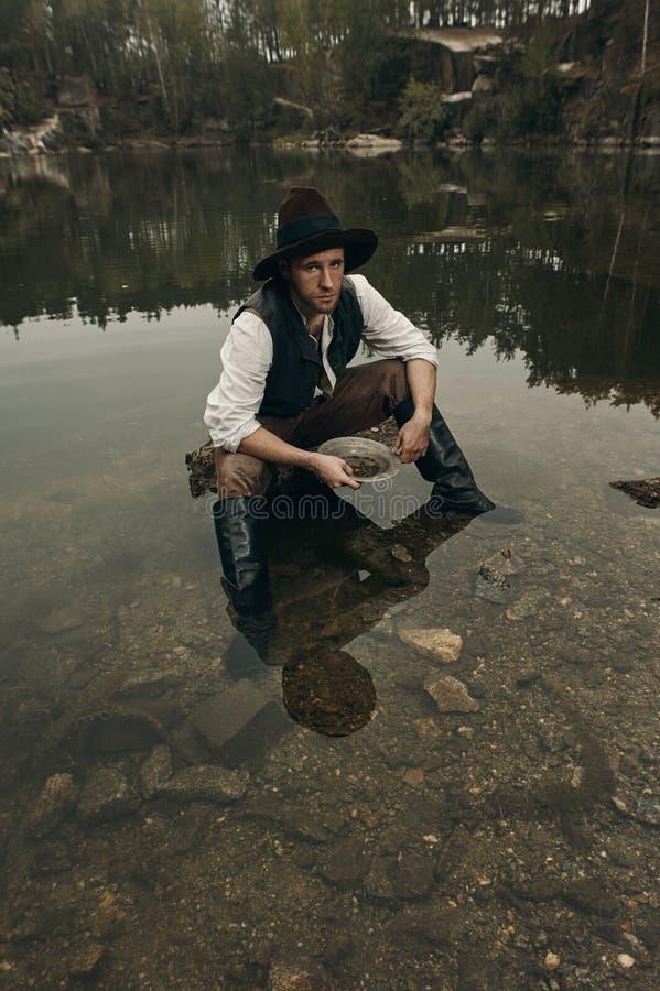 Le golddigger Unshaved lave l'or dans le lac avec la banque rocheuse photo stock