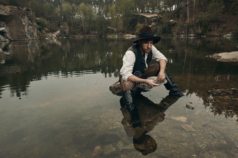 Le golddigger Unshaved lave l'or dans le lac avec la banque rocheuse image stock