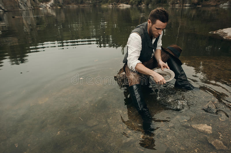 Le golddigger Unshaved lave l'or dans le lac avec la banque rocheuse image libre de droits
