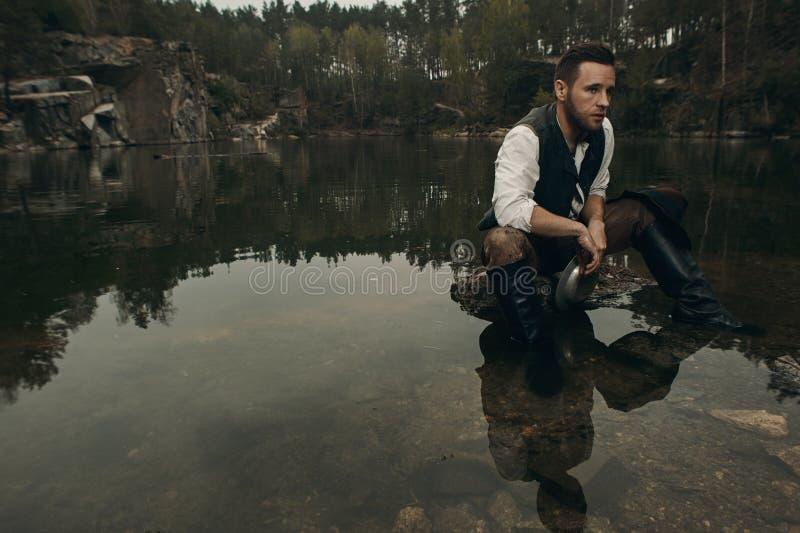 Le golddigger Unshaved lave l'or dans le lac avec la banque rocheuse photos libres de droits