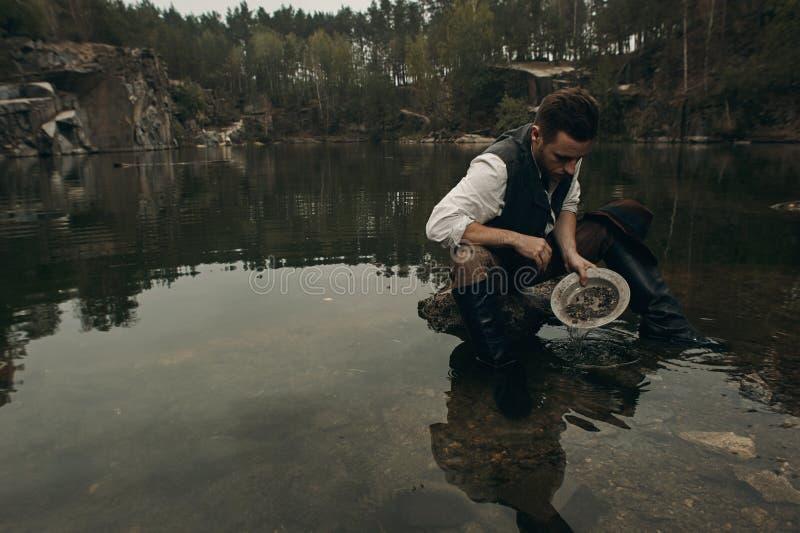 Le golddigger Unshaved lave l'or dans le lac avec la banque rocheuse photos stock