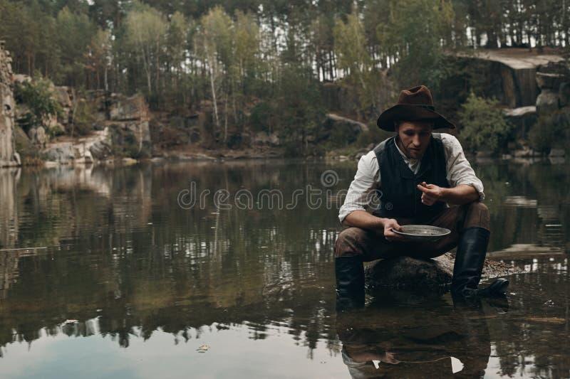Le golddigger Unshaved lave l'or dans le lac avec la banque rocheuse photographie stock