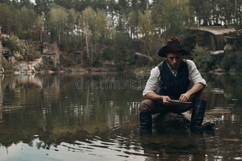 Le golddigger Unshaved lave l'or dans le lac avec la banque rocheuse images libres de droits